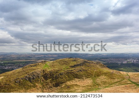 People on top of the hill in Holyrood Park in Edinburgh, Scotland. Park's highest point Arthur's seat is popular destination for hiking and enjoying nature.  - stock photo