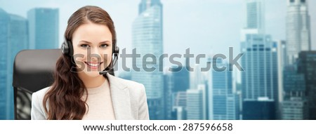 people, online service, communication and technology concept - smiling female helpline operator with headset over singapore city background - stock photo