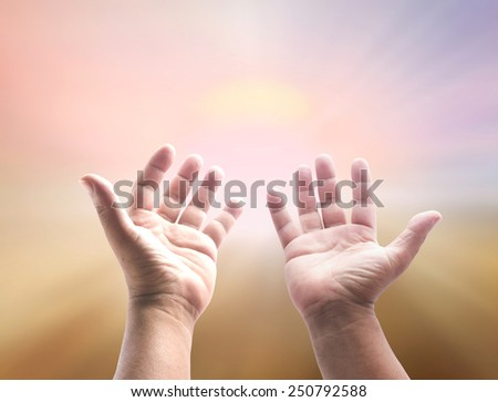 People open empty hands with palms up over blurred big sun on sunset background - stock photo