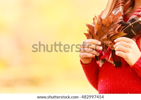 People outdoors concept. Lady with autumnal leaf. Close up picture of leaves in the park.