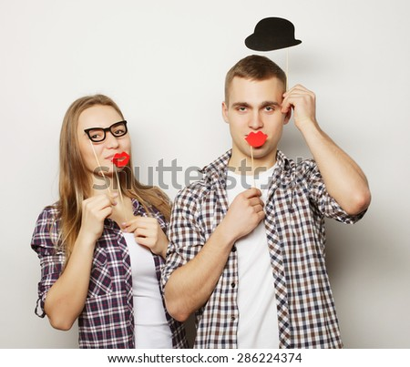 people, party, love and leisure concept - lovely couple holding party glasses and mustaches on sticks, over white  background - stock photo
