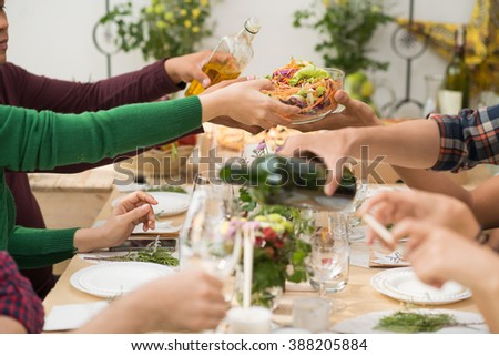 People passing bowl with vegetable salad at dinner