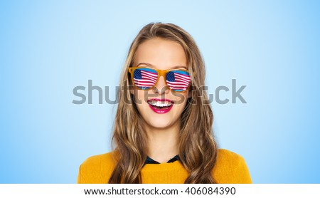 people, patriotism and nationality  concept - happy young woman or teen girl face in sunglasses with american flag over blue background - stock photo