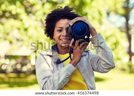 people, photography, technology, leisure and lifestyle - happy young african american female photographer looking to digital camera viewfinder in summer park - stock photo
