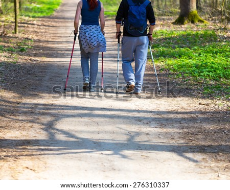 People play sport in forest. Nordic walking couple.