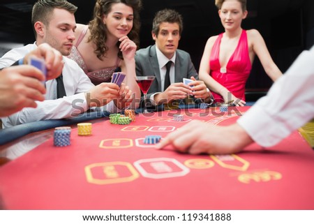 People playing exciting game of poker in casino - stock photo