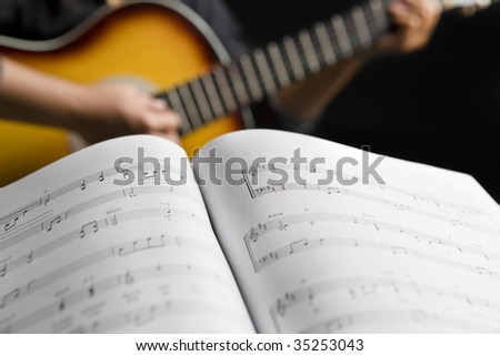People playing guitar with musical chords in dark room - stock photo