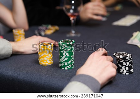 People playing poker. Players hands on table.