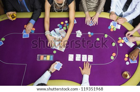 People playing poker woman grabbing money - stock photo