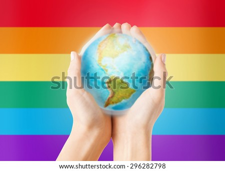 people, population and gay pride concept - close up of human hands with earth globe showing american continent over rainbow flag stripes background - stock photo
