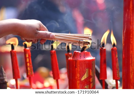 People prayers burning incense sticks on a red candle fire - stock photo