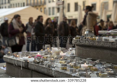 People praying and giving flowers and lighting candles on the steps of the town hall at Lyon, France about the terrorist bombing happens in France on 13th november - stock photo