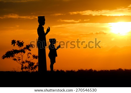 people  praying at the sunset. - stock photo