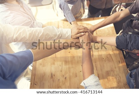 people putting their hands together for united, cooperation and teamwork concept, selective focus and vintage tone - stock photo