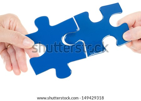 People putting two pieces of jigsaw together - stock photo