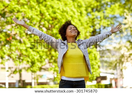 people, race, ethnicity and portrait concept - happy african american young woman with open arms in summer park - stock photo
