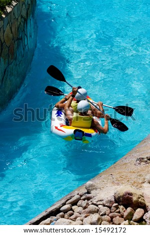 people rafting on fake waves in an amusement aqua park