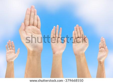 people raise hand on sky background - stock photo