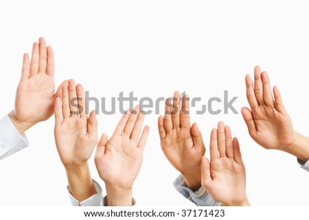 People raise hand to be picked up or to bid in an auction - stock photo