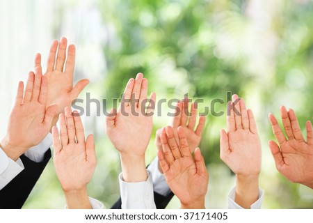 People raise their hands up to be picked up or to bid in an auction over green background - stock photo