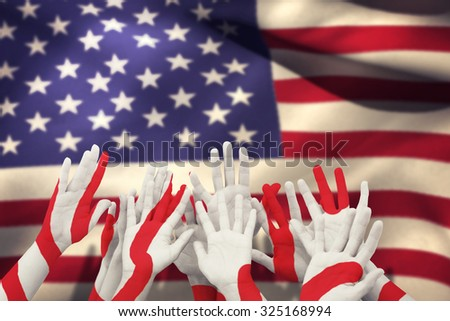 People raising hands in the air against close-up of american flag