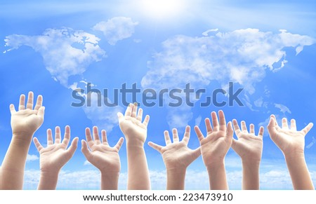 People raising hands on world map of clouds background. International Volunteer Day for Economic and Social Development, International Human Solidarity, Human Rights Day, World Religion Day concept. - stock photo