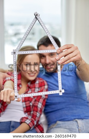 people, real estate and family concept - close up of happy couple looking through house shape made of ruler at home - stock photo