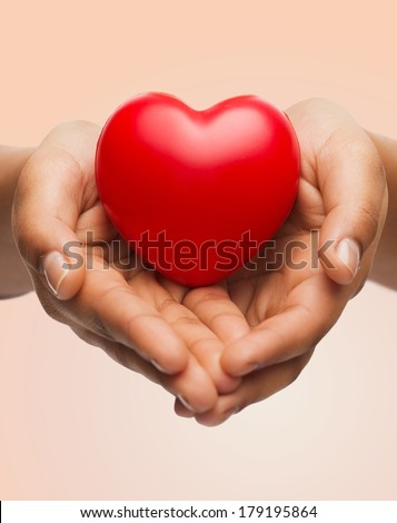 people, relationship and love concept - close up of womans cupped hands showing red heart - stock photo