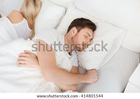 people, relationship difficulties, conflict and family concept - couple sleeping back to back in bed at home - stock photo