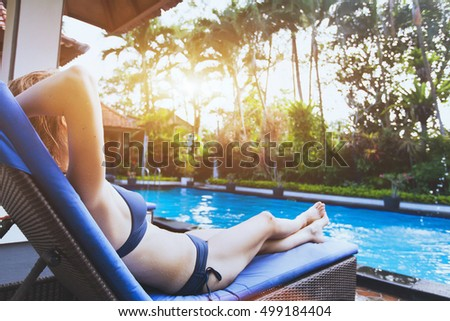 people relaxing in luxury tropical resort hotel near swimming pool