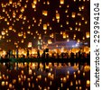 People release sky lanterns to pay homage to the triple gem: Budhha, Dharma and Sangha during Yi Peng festival. - stock photo