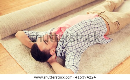 people, repair and renovation concept - happy man lying carpet or rug on floor at home - stock photo