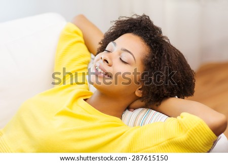 people, rest, comfort and leisure concept - happy african young woman relaxing or dreaming at home - stock photo