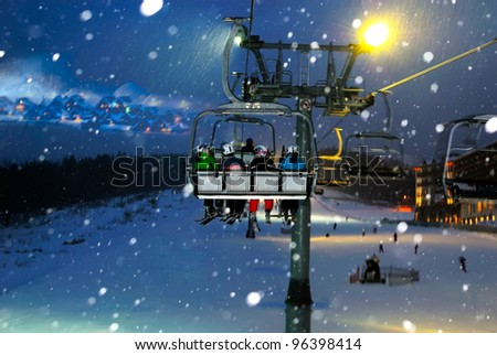 people ride in the chair lift, elevator, night landscape - stock photo