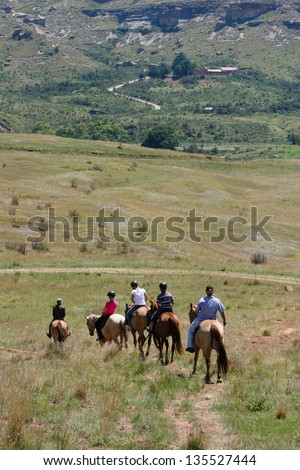 people riding horses in the mountains