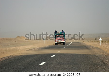People riding on the roof of an old truck on a sandy road