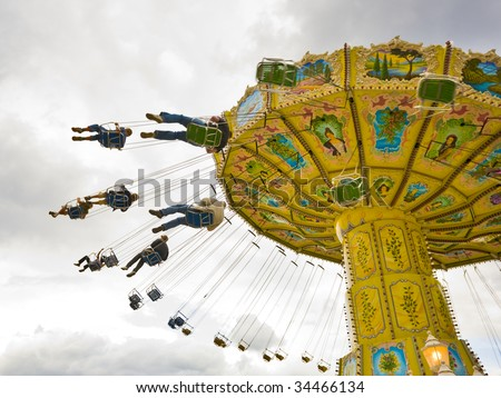 people riding the spinning swing at fairground - stock photo