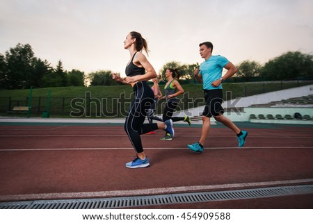 People running at the stadium. Group fitness training  - stock photo