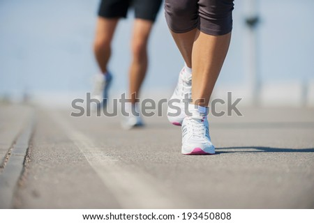 People running.  Close-up image of woman and man running along the running track  - stock photo