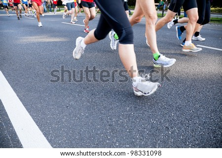 People running fast in a city marathon on a street - stock photo