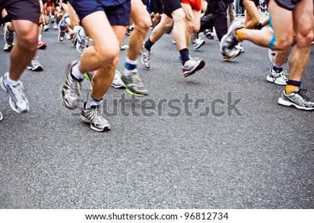 People running in city marathon on streets, sport and fitness on road - stock photo