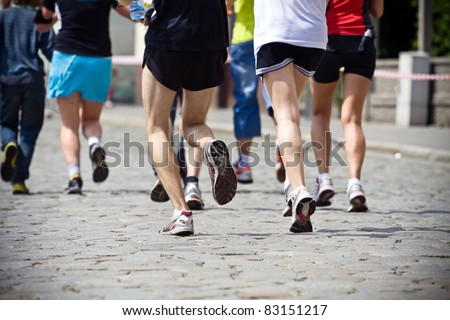People running in marathon on city streets, legs and runners - stock photo