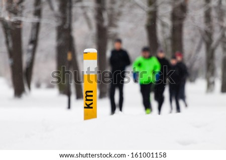 People running in park on snowy winter. Man runner jogging white snow in cold weather nature in forest. - stock photo