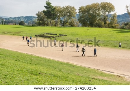 People running on an ancient stadium. Ancient Olympia, Greece. - stock photo