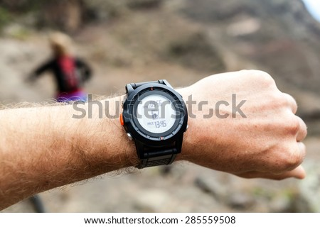 People running on mountain trail and looking at sports watch healthy lifestyle. Checking GPS position, performance or heart rate pulse and training working out. Sport and fitness outdoors in nature. - stock photo