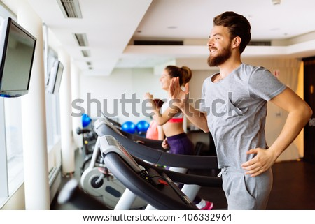 People running on treadmill in gym doing cardio workout - stock photo