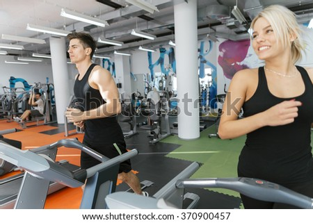 People running on treadmills in gym to keep body in shape