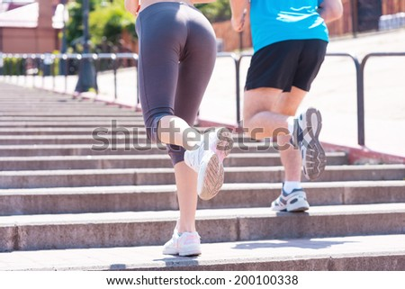 People running.  Rear view of woman and man running along the stairs  - stock photo