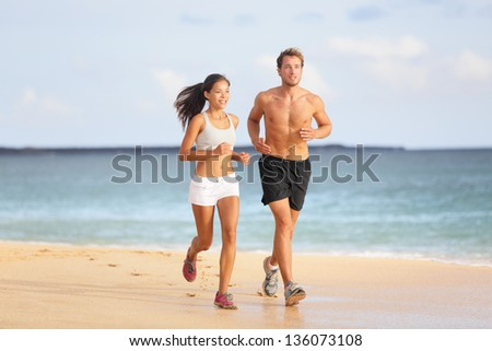 People running - young couple jogging on beach. Attractive fit sporty young couple runners side by side on the beach in the summer sunshine enjoying the fresh air as they train together - stock photo