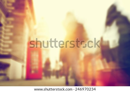 People rush on a busy street of London. Blur, defocused. Sun shining. - stock photo